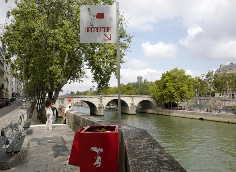 Women take photos on the Seine river banks on the Ile de la Cite where an urinal has been installed, Tuesday, Aug.14, 2018 in Paris. Some residents have written to the town hall to demand its removal from this touristic area not far away form Notre Dame Catheral. (AP Photo/Michel Spingler)