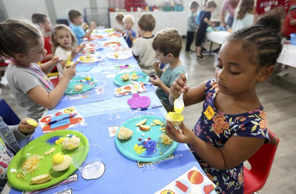 Alexis Alseme, 5, decorates cupcakes during the Dubuque Leisure Services' preschool cafe event at Allison-Henderson Park on Friday, June 22, 2018 in Debuque, Iowa. Organizers of the activities said teaching children kitchen essentials helps them learn lifelong skills that grant them independence and inform them about nutrition. (Jessica Reilly/Telegraph Herald via AP)