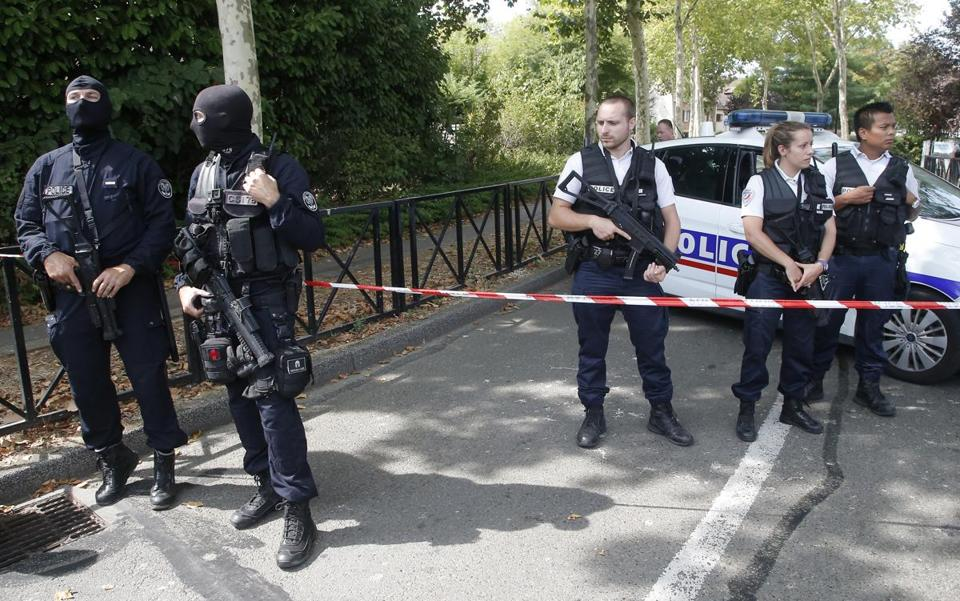 French hooded police officers guarded the area with other police officers after a knife attack Thursday in Trappes, west of Paris.