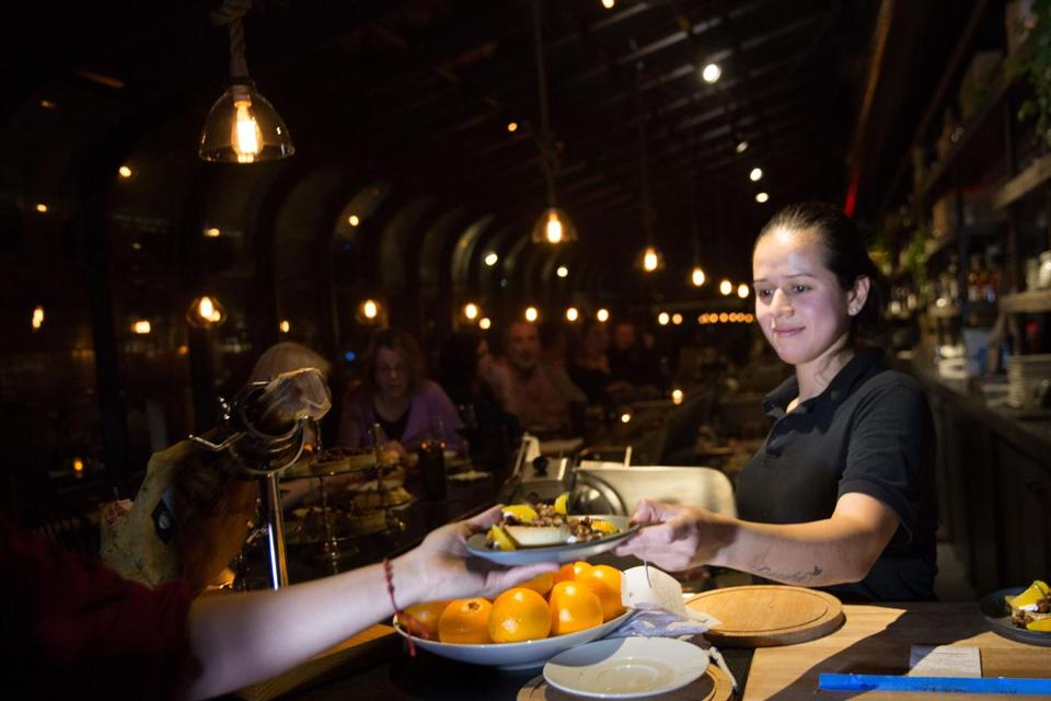 La Bodega cook Keara Garcia passed a dish off to a server in the front of the house prep station.