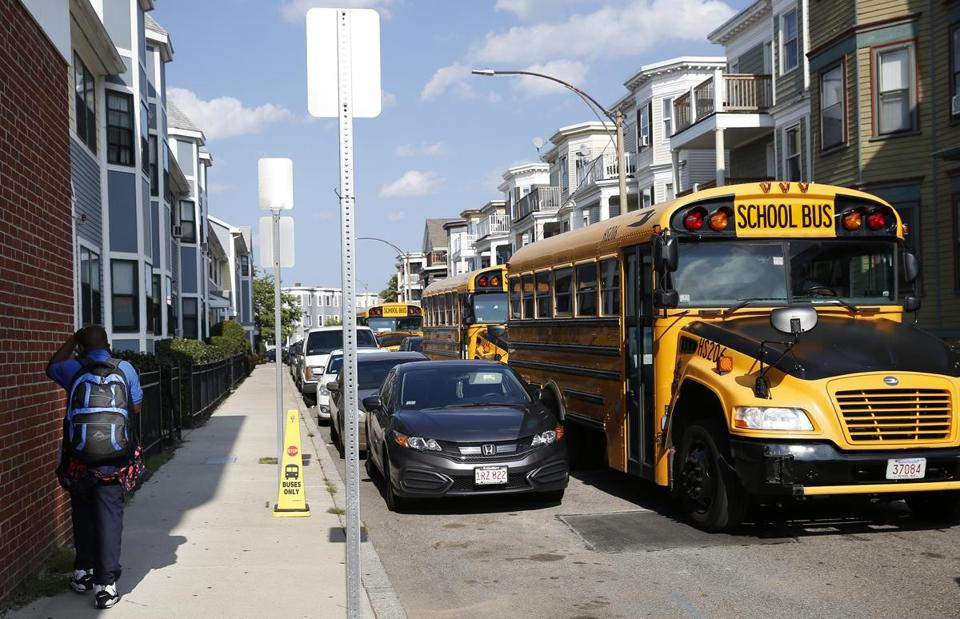 A student walked past school buses outside Codman Academy in Dorchester on Wednesday.