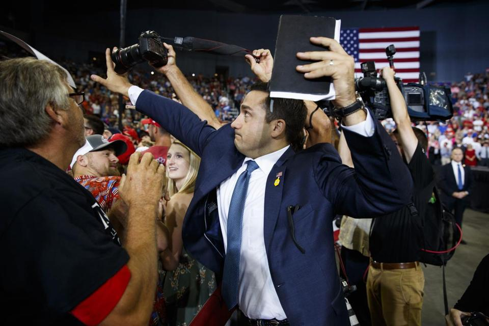 A staff member for President Donald Trump blocked a camera as a photojournalist attempted to take a photo of a protester during a campaign rally in Evansville, Indiana.