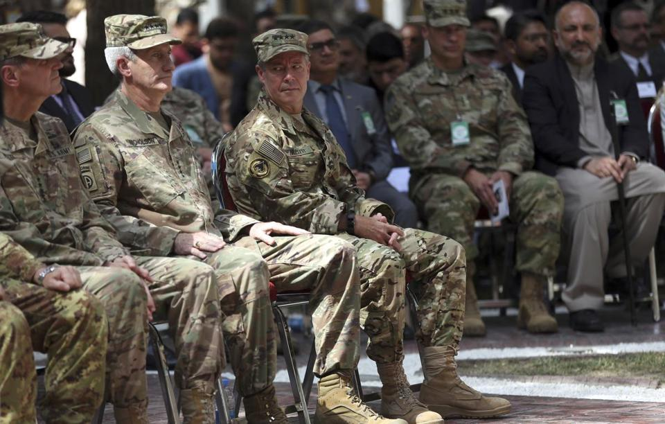 Outgoing US Army General John Nicholson (second from left) listened as incoming General Austin Scott Miller (third from left) looked at him before the change of command ceremony started at Resolute Support headquarters in Kabul on Sunday. Miller assumed command of the 41-nation NATO mission in Afghanistan following a hand-over ceremony.