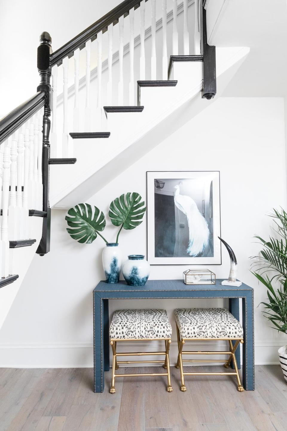 In the entry, faux-bamboo stools with hand-carved feet from Society Social tuck neatly away under the console when not in use. The framed peacock print by Christine Lindstrom is from Artfully Walls.