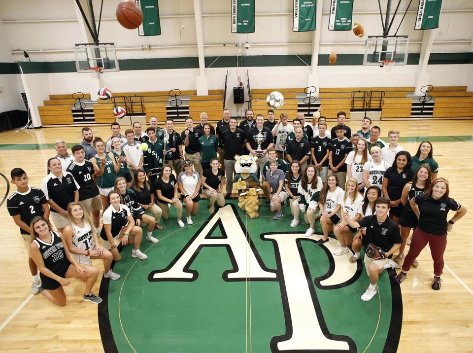 Austin Prep athletes and athletics staff members pose in their gym in Reading, Mass., Tuesday, Sept. 4, 2018. (Winslow Townson for The Boston Globe)