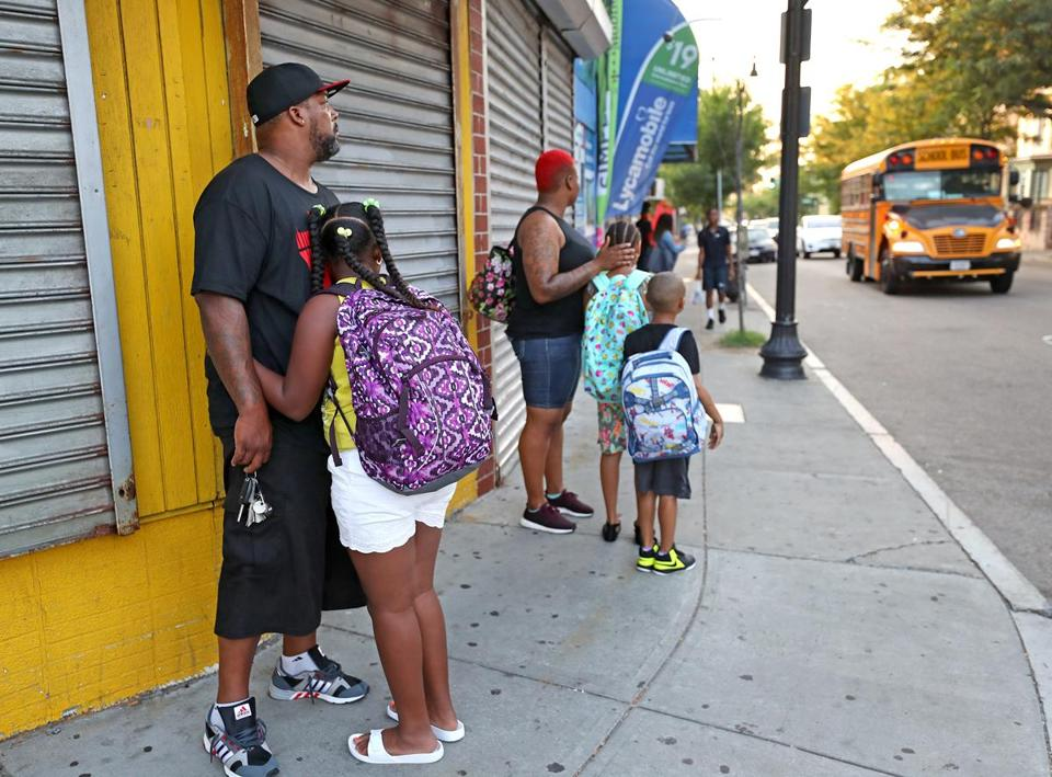 Parents waited with their children for a bus that was running late on Geneva Avenue on Thursday.
