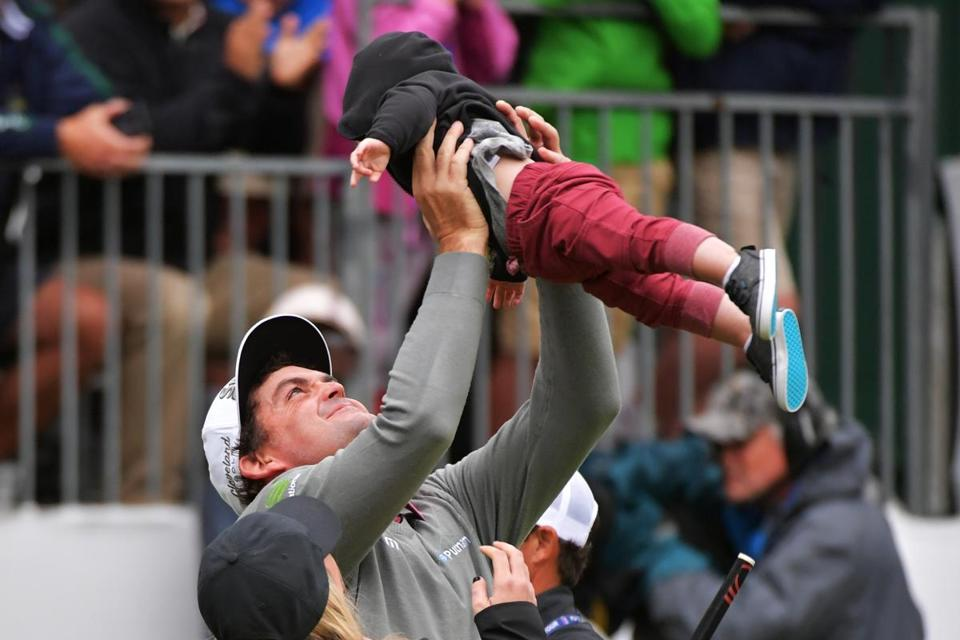 Keegan Bradley holds up his son Logan after winning the BMW Championship at Aronimink Golf Club.