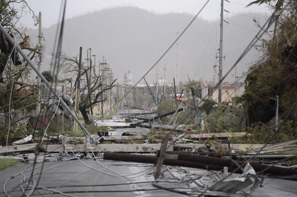 Utility poles and lines were toppled on a road after Hurricane Maria hit Puerto Rico last year.