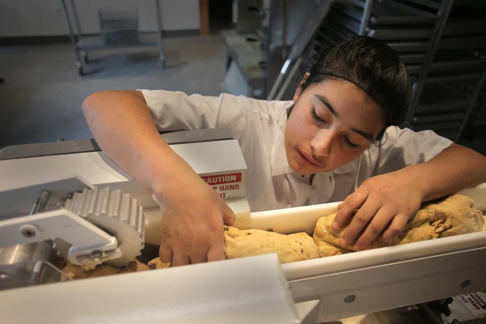 Baker Yesica Mendez loaded dough into a machine that cuts and shapes it into bagels.