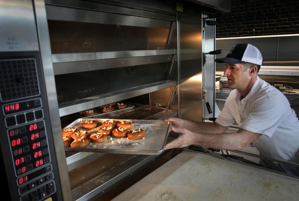 Baker Tony Rosenfeld loaded bagels topped with cheese into the oven.