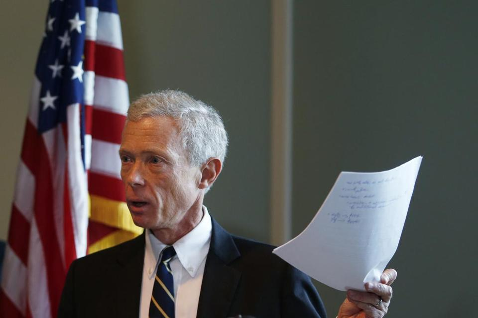 New Hampshire Attorney General Gordon MacDonald held up a copy of the agreement made with St. Paul's School during a press conference in Concord, N.H., Thursday.