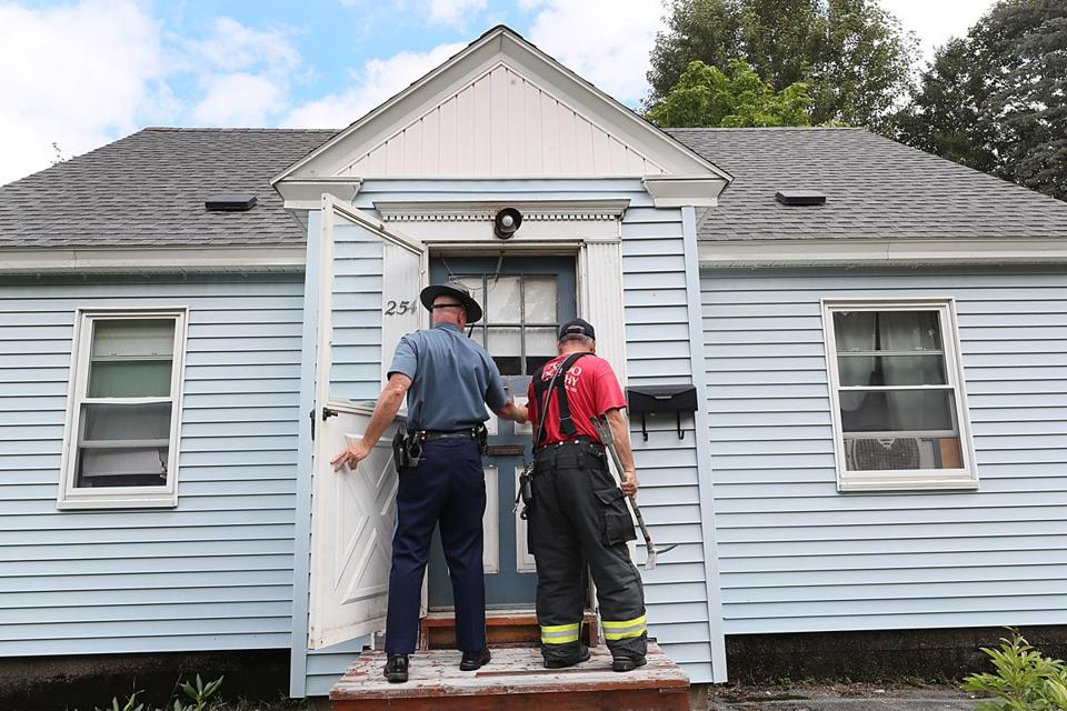 Firefighters and law enforcement personel accompanied Columbia Gas workers on Pleasant Street to gain access to home via locksmiths and going in through windows, to get check for gas leaks and to lock down the gas meters.