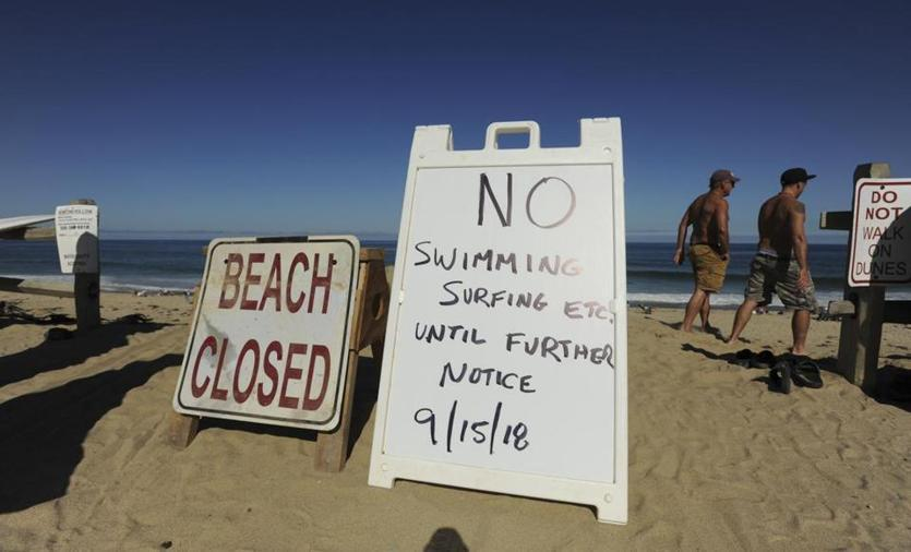 Signs at the top of the dune at Newcomb Hollow Beach alerted visitors that the beach was closed to swimming Saturday.