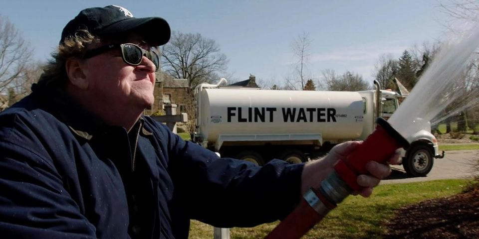"Michael Moore sprays water from Flint, Mich., on the governor's lawn in ""Fahrenheit 11/9."""