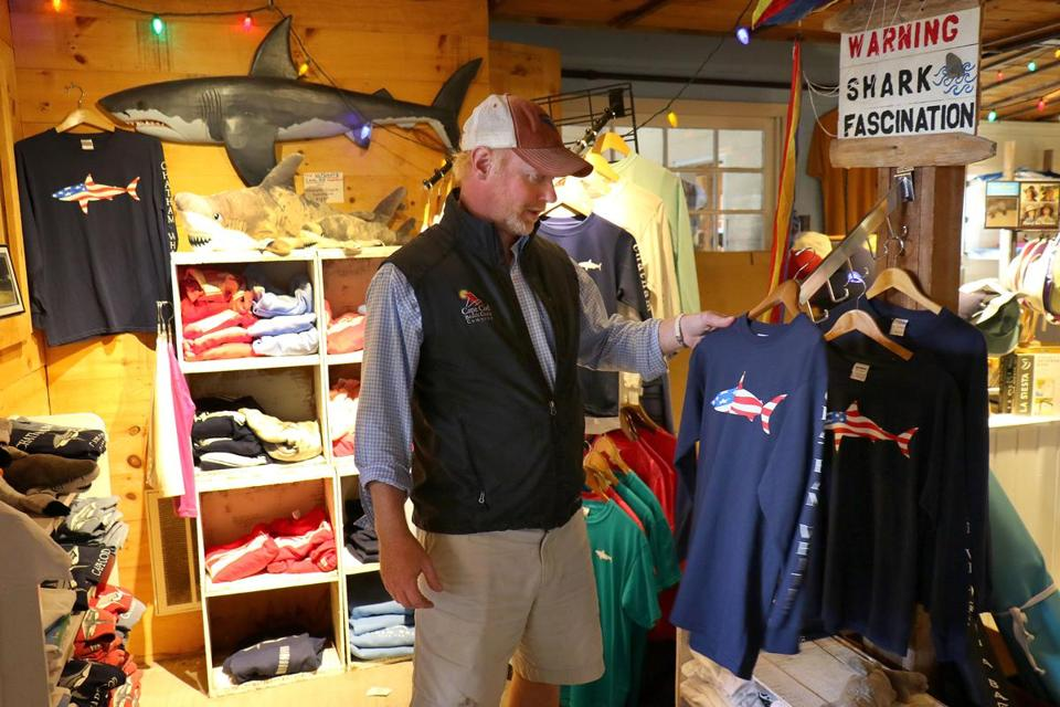Harwich-09/20/18 How will the shark attack death affect Cape Cod's embrace of everything shark. Justin Labdon, owner of Chatham Whites with some of the shirts they sell in their store. Photo by John Tlumacki/Globe Staff(business)