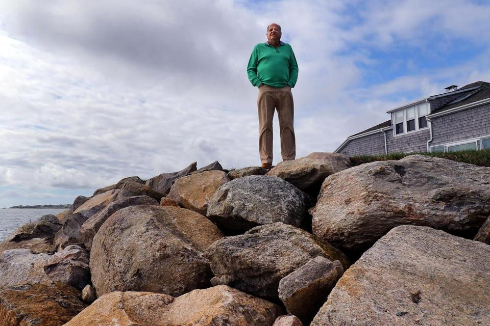 Gerald Milden is against the dredging in Chatham Harbor and said that it accelerated the loss of sand in front of his home, causing erosion. He stood near the huge boulders that were added to his oceanfront property.