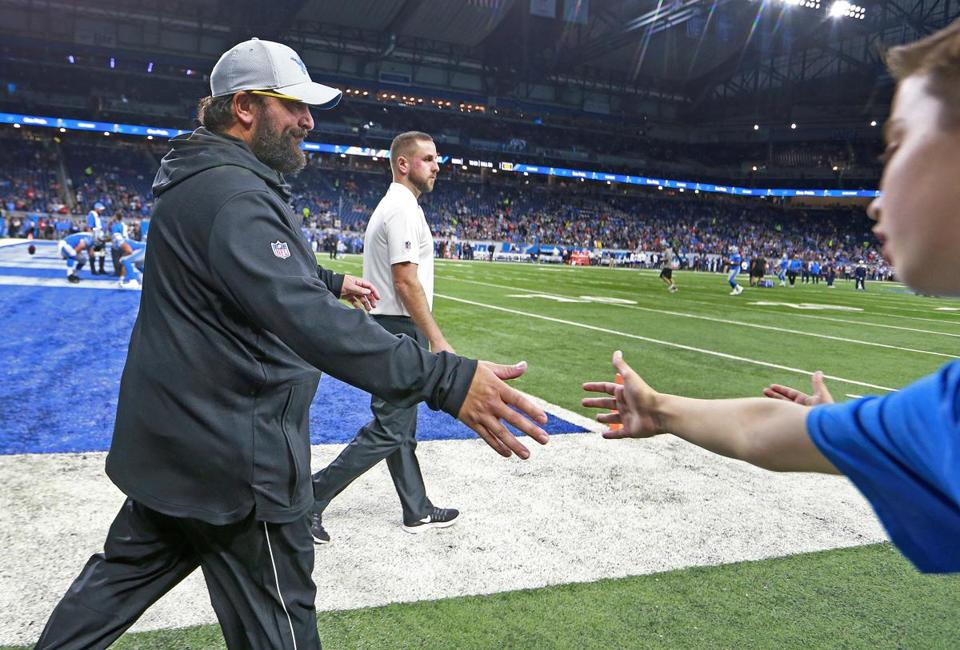 Matt Patricia gives a hand to a young fan as he comes onto the field for pregame warmups.