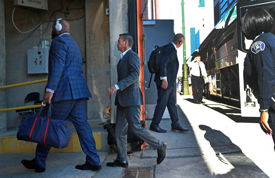 Alex Guerrero (center) is pictured as he gets off the team bus and heads into the stadium with players, including Marcus Cannon (left).