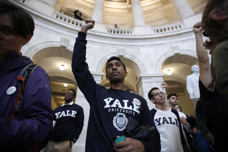 Yale student Jishian Ravinthiran, center, raises his fist during a protest against Judge Brett Kavanaugh in the Russell Senate Office Building Rotunda, on Capitol Hill, Monday, Sept. 24, 2018 in Washington. A second allegation of sexual misconduct has emerged against Judge Brett Kavanaugh, a development that has further imperiled his nomination to the Supreme Court, forced the White House and Senate Republicans onto the defensive and fueled calls from Democrats to postpone further action on his confirmation. President Donald Trump is so far standing by his nominee. (AP Photo/Alex Brandon)