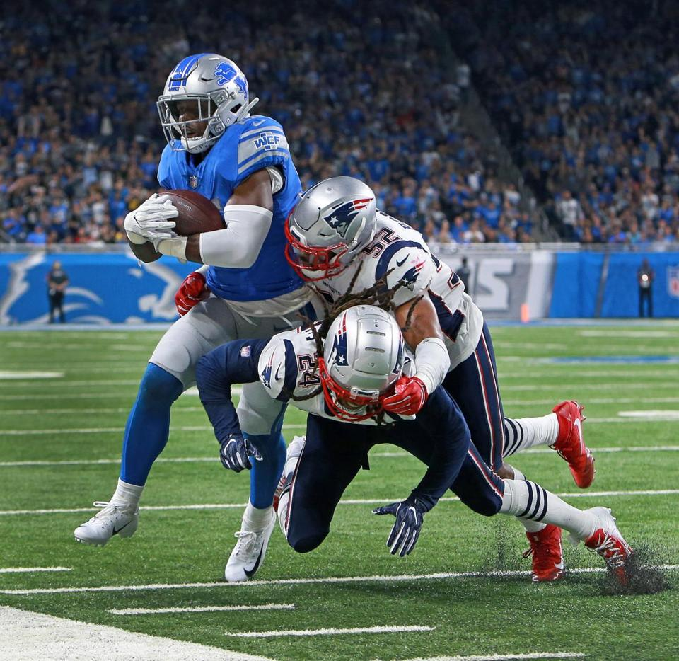 Theo Riddick drags Elandon Roberts (52) andStephon Gilmore (24) out of bounds as he gains some first quarter yardage that set up a Detroit field goal.