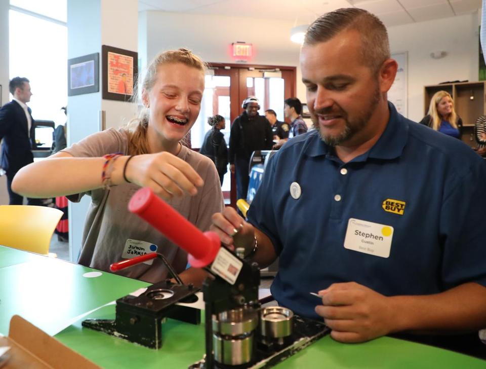 Siroun Johnson, 14, taught Best Buy's Stephen Gustin how to make buttons during Tuesday's opening of the new headquarters of the Clubhouse Network in Roxbury.