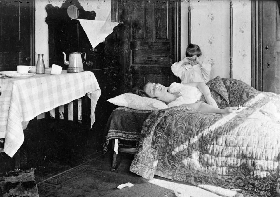 In this November 1918 photo made available by the Library of Congress a girl stands next to her sister lying in bed. The girl became so worried she telephoned the Red Cross Home Service who came to help the woman fight the influenza virus. No one knows the ultimate origin of that terrifying 1918 flu. But researchers hope they're finally closing in on stronger flu shots, ways to boost much-needed protection against ordinary winter influenza and guard against future pandemics at the same time. (Library of Congress via AP)