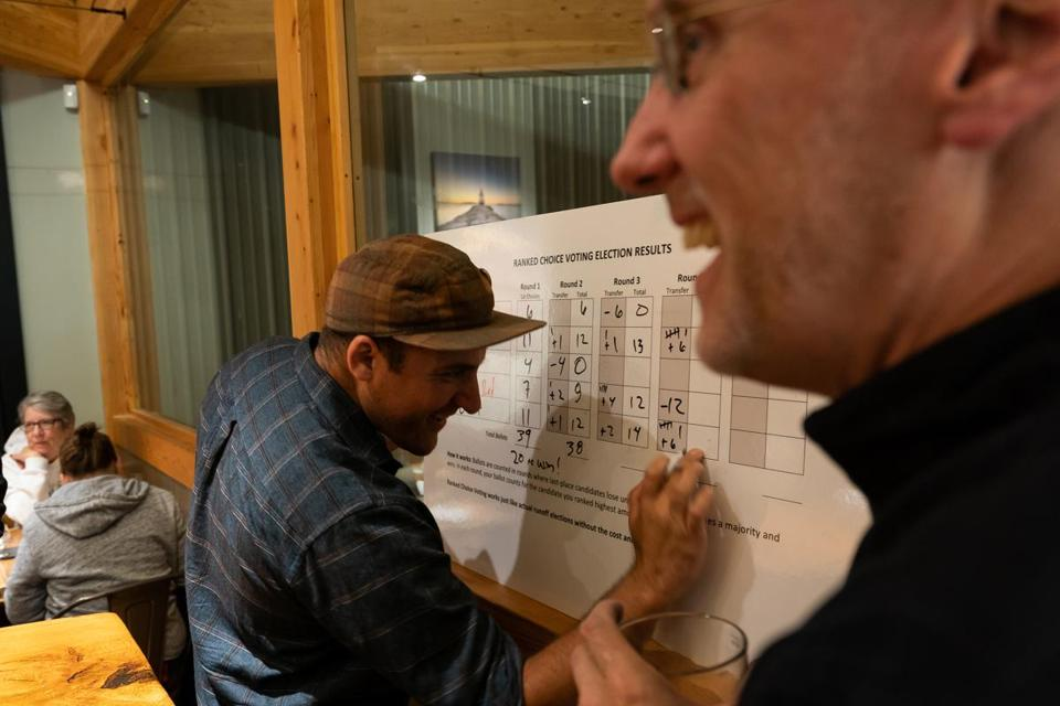 Scarborough, ME, United States -- Grayson Lookner, events coordinator, laughs with Mark Violette, right, while tallying the votes during a ranked choice beer election organized by the Committee for Ranked Choice Voting in Maine at Nonesuch River Brewery in Scarborough, ME on Monday, September 24, 2018. The vote ended in a tie between the IPA and the Stout and was broken by a ballot that was filled out by an employee of Nonesuch. The committee holds beer elections to educate people on how ranked choice voting works in a real election. (Yoon S. Byun for the Boston Globe) Slug: Reporter: Jessie Scanlon LOID: 8.4.3310032058