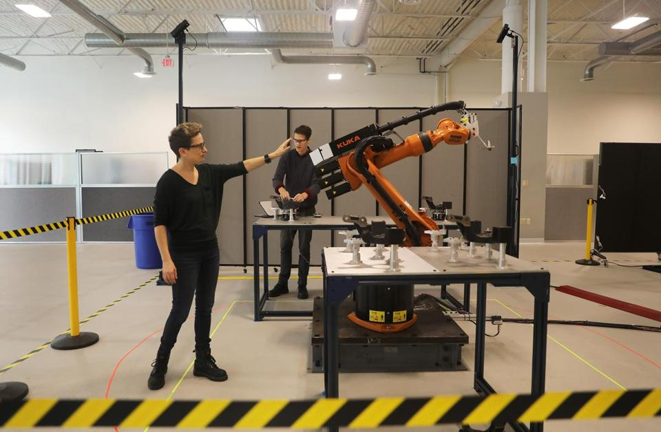 Waltham, MA - 9/26/18 - Clara Vu (cq), left, is vice president of engineering and co-founder of Veo Robotics, Inc., in Waltham. She directs a demonstration that shows how industrial robots work with people. Senior software engineer Paul Schroeder (cq), rear, attaches bolts to an automotive hub and steering knuckle that the Kuka KR-16 robot put in place, in this work cell. Photo by Topic: 05robots Reporter: Katie Johnston
