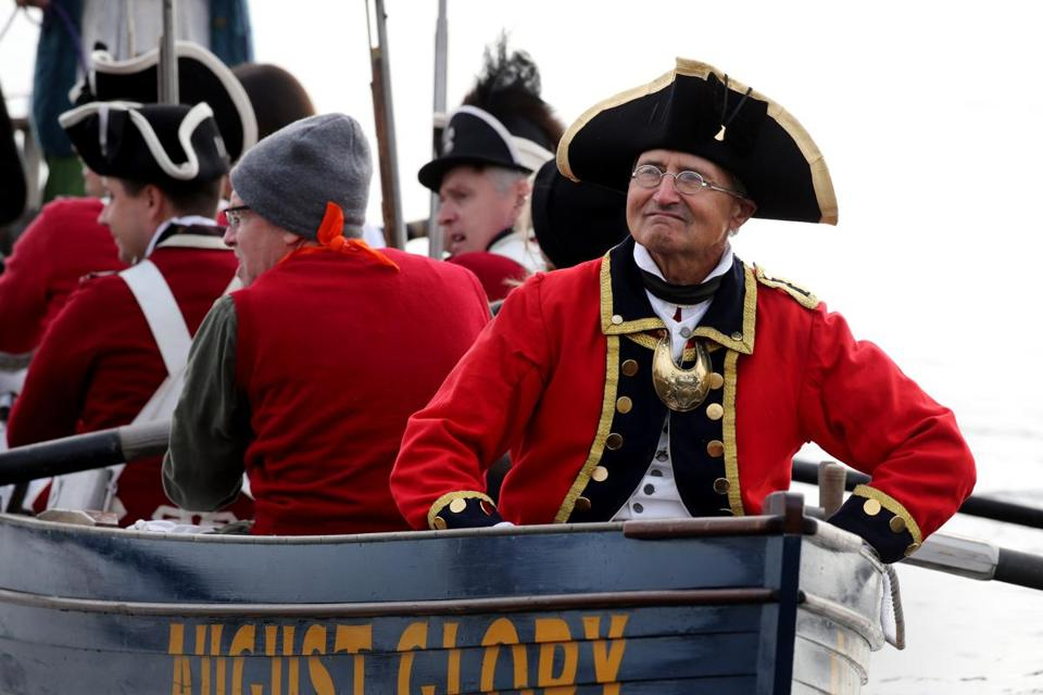 Boston, MA - October 06, 2018: British reenactors Ensign Peter Pechulis is in the bow of a long boat arriving at Long Wharf during ÒBoston Occupied: An Insolent ParadeÓ in Boston, MA on October 06, 2018. (Exactly 250 years after British soldiers landed in Boston Harbor for the first time, Bostonians this weekend will once again be able to yell, ÒThe Redcoats are coming!Ó A troupe of about 150 Redcoat reenactors will land at Long Wharf Saturday morning and march into downtown Boston to commemorate the sestercentennial anniversary of when the red-clad British nationals first arrived in the city in October of 1768. The reproduction of the soldiersÕ arrival and the march that will follow it comprise ÒBoston Occupied: An Insolent ParadeÓ Ñ the signature event organized by Revolution 250, a group of organizations, including the Massachusetts Historical Society, working together to commemorate the 250th anniversary of the events that eventually culminated in the coloniesÕ independence from Britain.) (Craig F. Walker/Globe Staff) section: Metro reporter: