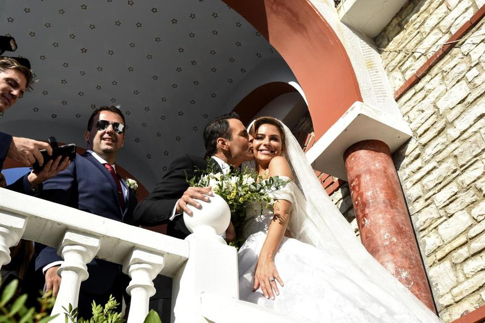 AfterBuzz TV founder Undergaro, third left, kisses TV personality Maria Menounos after their Orthodox wedding ceremony at a church in the village of Akovo, south west of Athens, Saturday, Oct. 6, 2018. (AP Photo/Dimitris Lampropoulos)