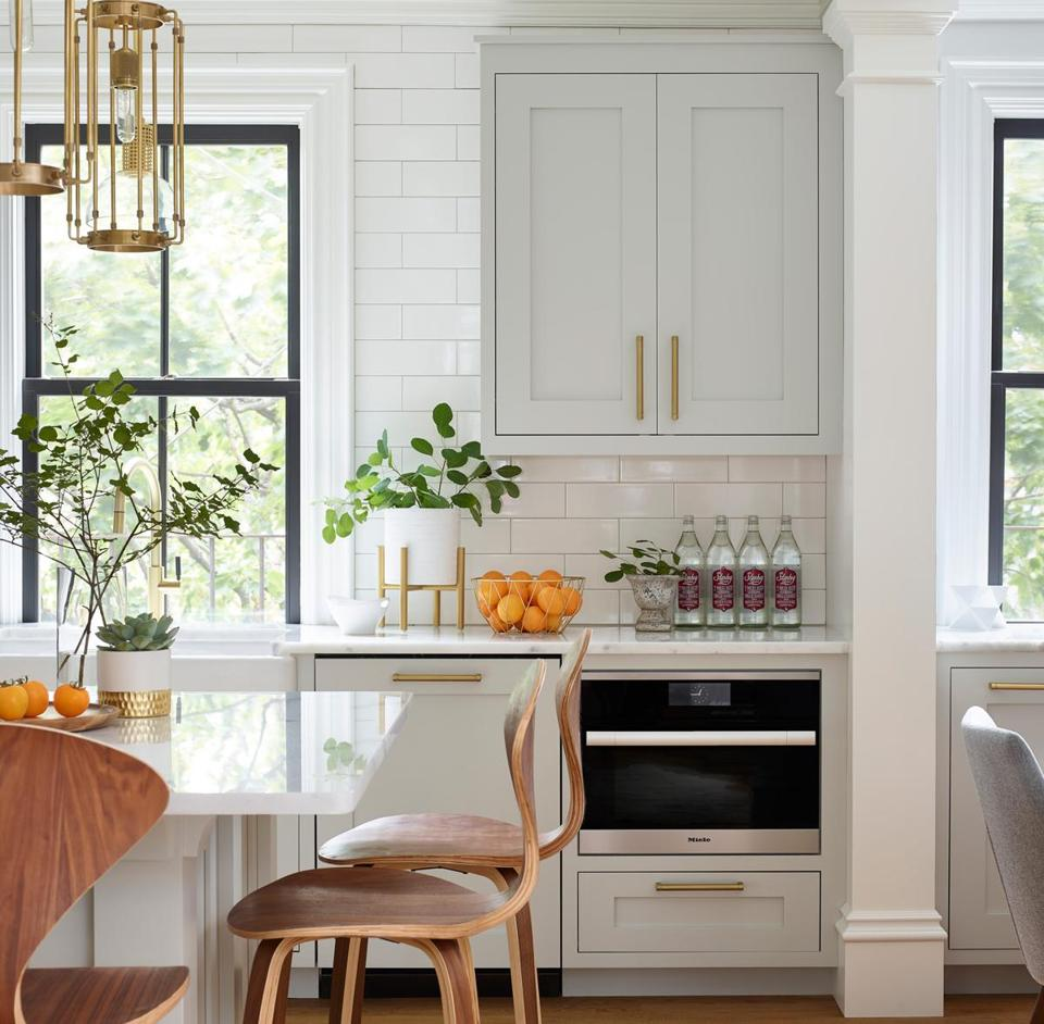 "esigner Karen Swanson chose the aged-brass Hyde Park pendants by Hudson Valley Lighting to anchor the island. ""The long shape fills the space, and the cage-type style keeps things airy,"" she says."
