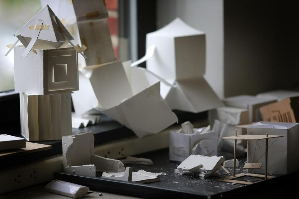 Models of wood, paper, metal, and plaster are strewn across the lab.