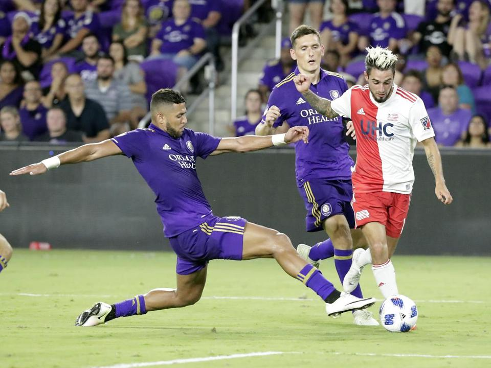 Orlando City's Amro Tarek, left, goes after the ball against New England Revolution's Diego Fagundez, right, during the second half of an MLS soccer match, Saturday, Aug. 4, 2018, in Orlando, Fla. (AP Photo/John Raoux)