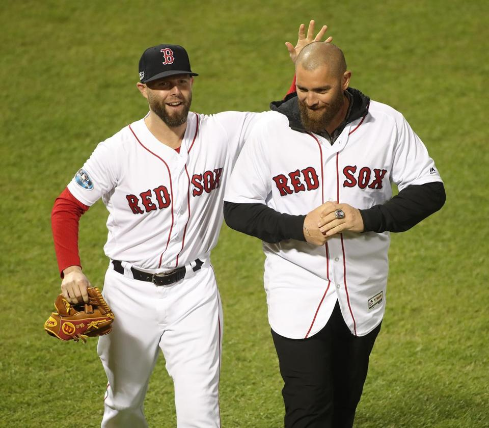 Boston, MA 10/14/18: Red Sox Dustin Pedroia (left) feels the former Red Sox Jonny Gomes after Gomes has taken the ceremonial place before the second game of the ALCS. Boston Red Sox hosted the Houston Astros in the second ALCS game at Fenway Park on Sunday, October 14, 2018. [Stan Grossfeld / Globe staff]