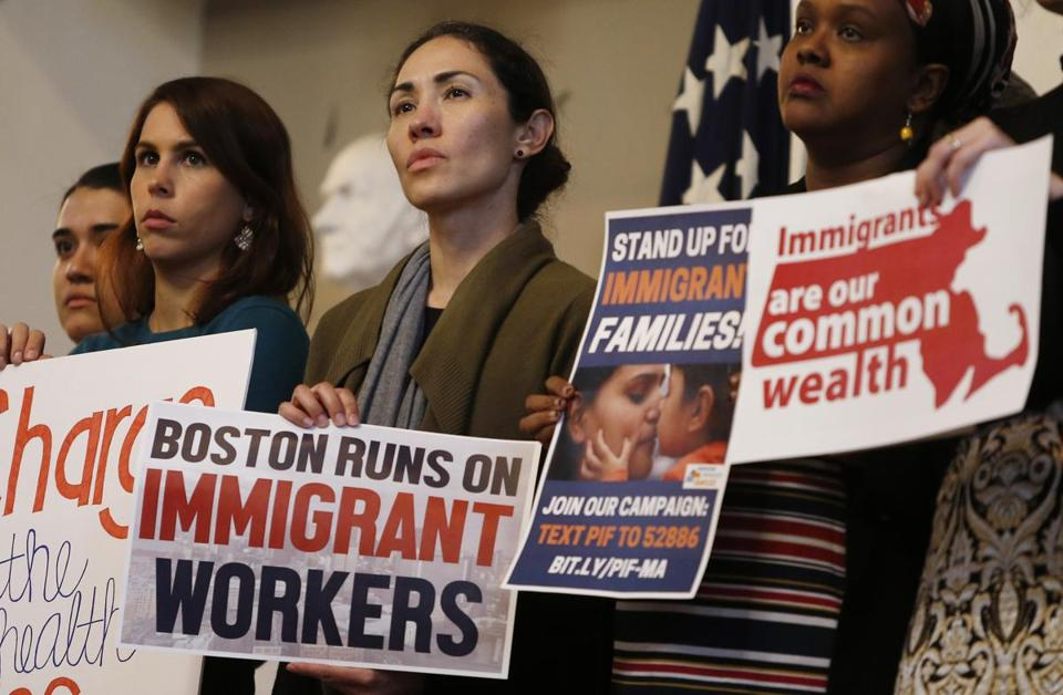 "People held signs onstage as Mayor Walsh hosted a rally supporting immigrant families to speak out against the Trump Administration's change to the ""public charge"" provision which would increase the number of government programs that count against an immigrant when applying for a visa or green card. (Jessica Rinaldi/Globe Staff) Topic: 16immigrant Reporter:"