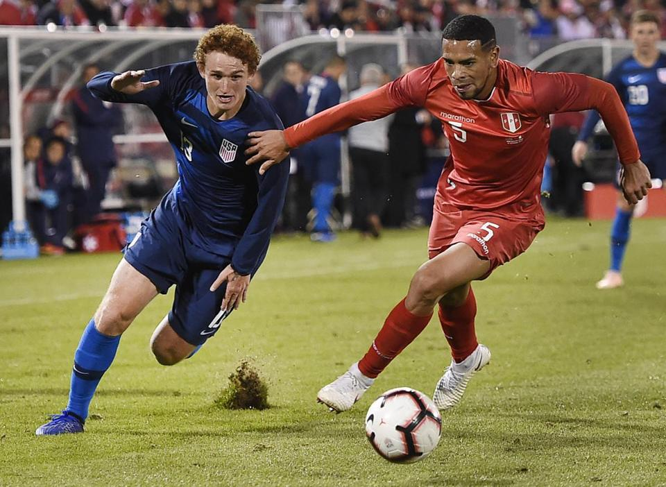 United States' Josh Sargent (13) and Peru's Alexander Callens (5) vie for the ball during the second half of an international friendly soccer match in East Hartford, Conn., Tuesday, Oct. 16, 2018. (AP Photo/Jessica Hill)