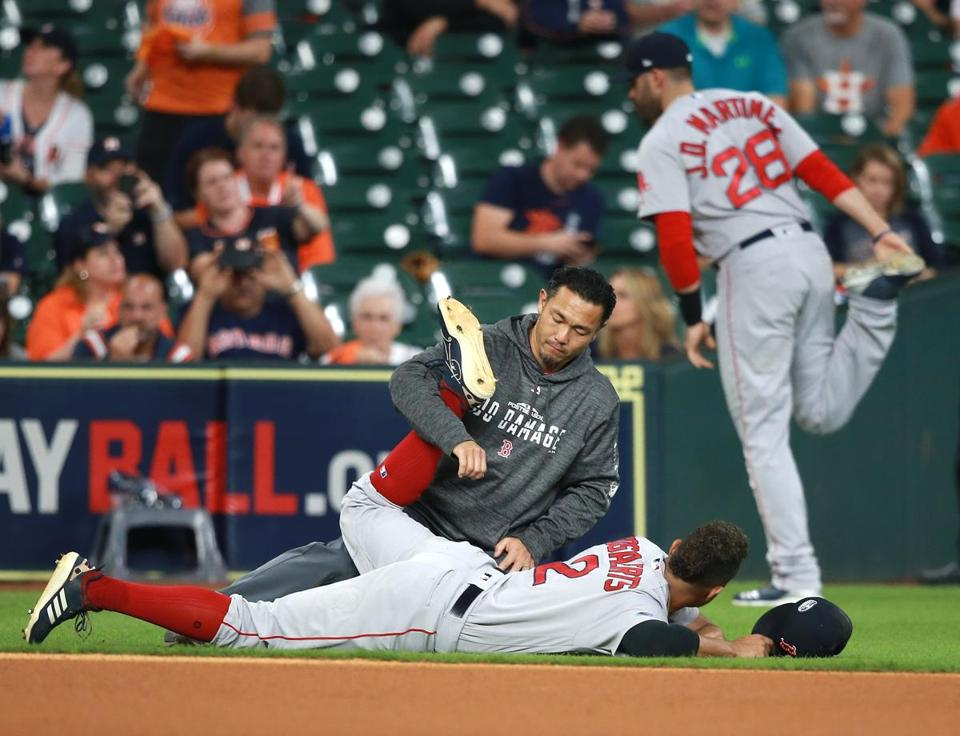 Red Sox players Xander Bogaerts (on ground) and J.D. Martinez had his own methods of stretching prior to Game 5.