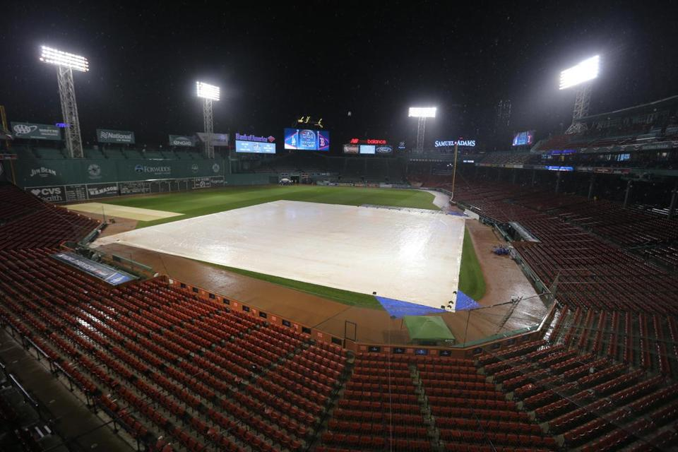 The infield tarp covers the field as a storm passes over Fenway Park before the game.