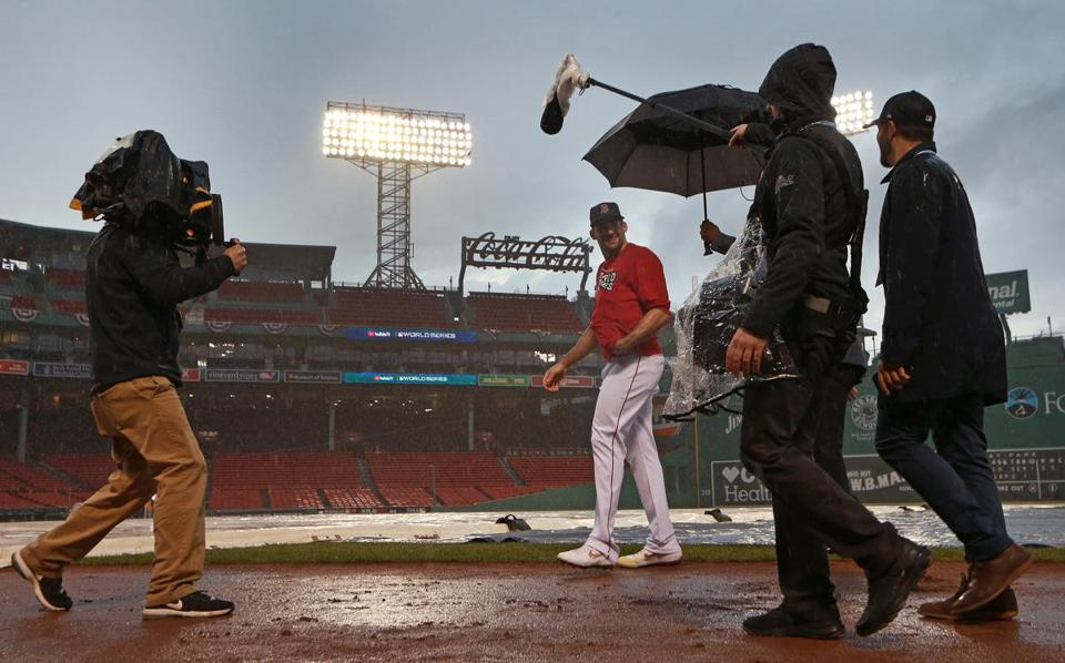 Boston, MA 10-23-18: Red Sox pitcher Nathan Eovaldi is shadowed by an umbrella toting camera crew as heavy rain fell in the area around 4:30 pm. The Boston Red Sox hosted the Los Angeles Dodgers in Game One of the World Series at Fenway Park. (