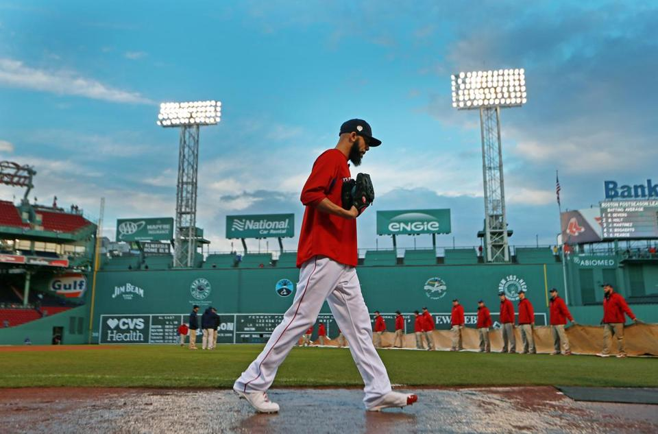 Boston, MA 10-23-18: After a rain storm moved through the area, Red Sox Game Two scheduled starting pitcher David Price walked on the wet dirt, while in the backround, the grounds crew, who had removed the tarp to clear it of standing water, were ready to put it back on over the infield. The Boston Red Sox hosted the Los Angeles Dodgers in Game One of the World Series at Fenway Park. (