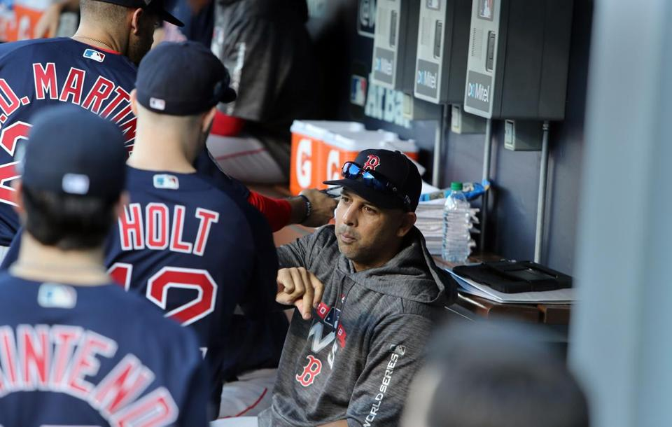 Red Sox boss Alex Cora in the dugout with players before Game 3.