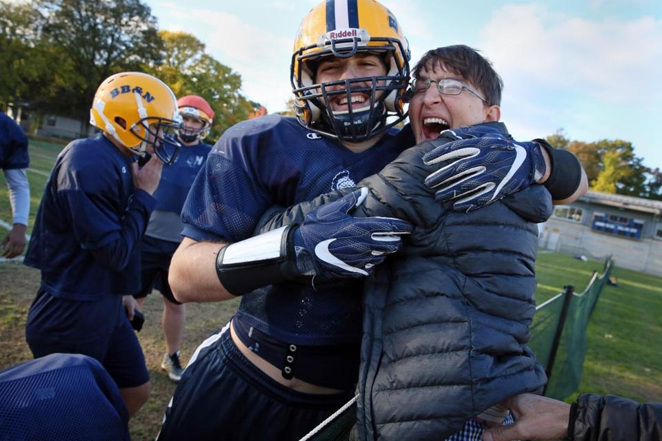 Cambridge, MA - October 25, 2018: Former Buckingham, Browne & Nichols School football player Zach McLeod, 27, is greeted by Tommy Maloney during practice at the school in Cambridge,MA on October 25, 2018. McLeod suffered a traumatic brain injury during a scrimmage 10 years ago, in 2008. He is still a presence at practices and games for the Knights. (Craig F. Walker/Globe Staff) section: sports reporter: kotsopoulos