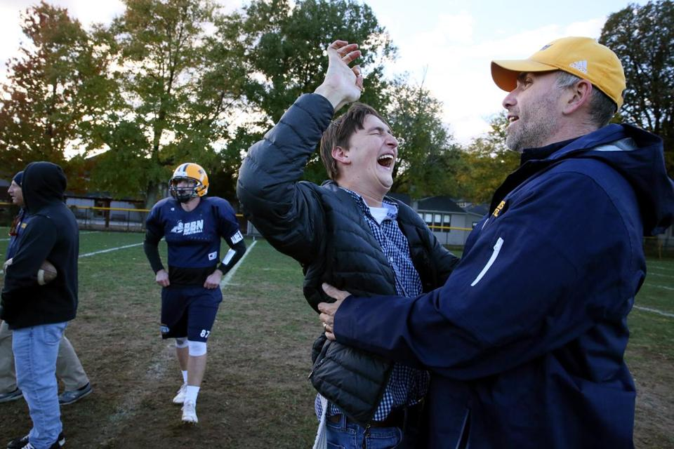 Former BB&N football player Zach McLeod is greeted by coach Mike Willey during practice at the school.