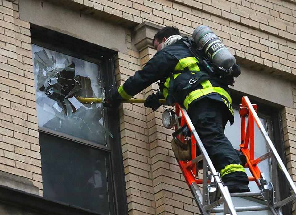A firefighter smashed a fifth-floor window.