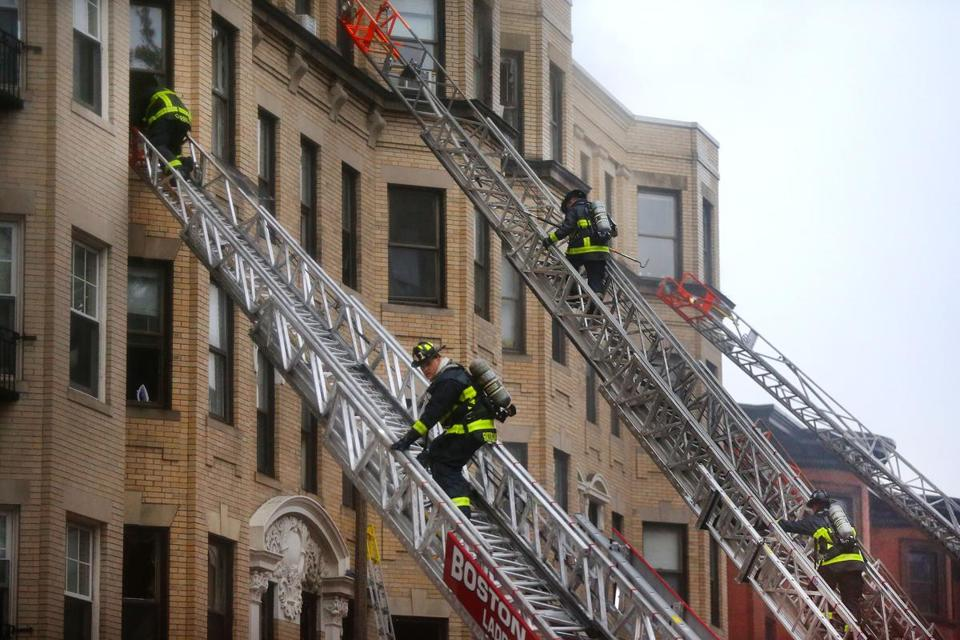 Firefighters climbed aerial ladders at the front of the building.