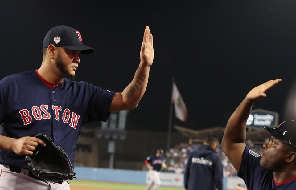 Eduardo Rodriguez gets a high five from pitching coach Carlos Febles after he knocked out the last shot in the fifth inning.