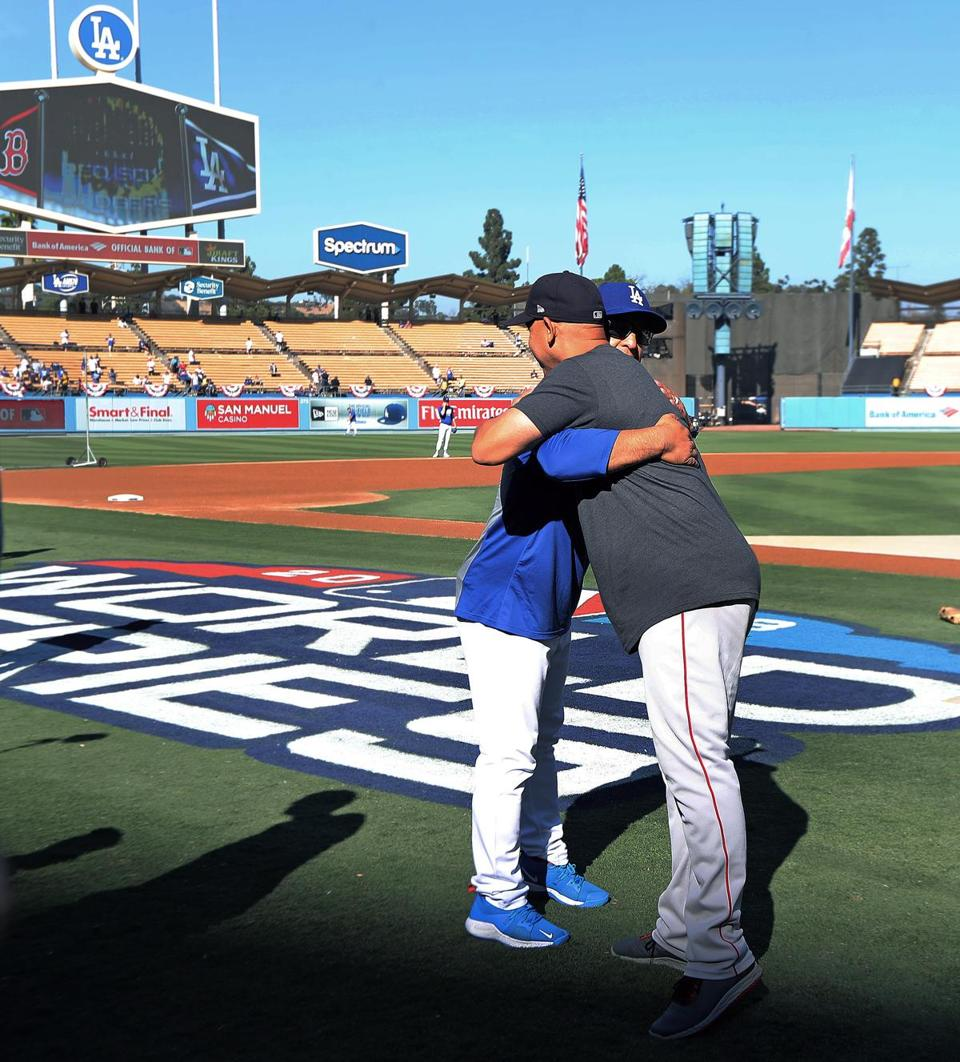 Dodgers manager Dave Roberts (left) and Red Sox manager Alex Cora (right) ran into each ohter by chance on the field around two and a half hours before the first pitch of Game 4 and they exhanged a hug.
