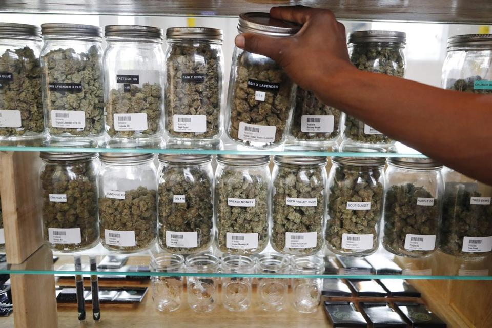 FILE - In this Tuesday, Oct. 2, 2018, file photo, a clerk reaches for a container of marijuana buds for a customer at Utopia Gardens, a medical marijuana dispensary, in Detroit. Backers of legalizing marijuana in North Dakota have high hopes voters will approve the drug just two years after they said yes to medicinal use. But they may be in for a bummer, since deep-pocketed outside groups so far haven't put a dime into the measure, suggesting they don't see it as a good bet. Meanwhile, opposition groups have spent heavily to publicize their concerns that approval would mean big societal problems. (AP Photo/Carlos Osorio File)