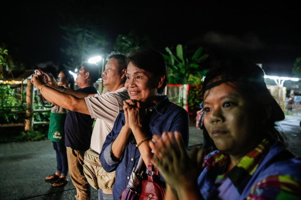 Onlookers watch and cheer at a hospital in Chiang Rai city as ambulances deliver boys rescued from a cave in northern Thailand.