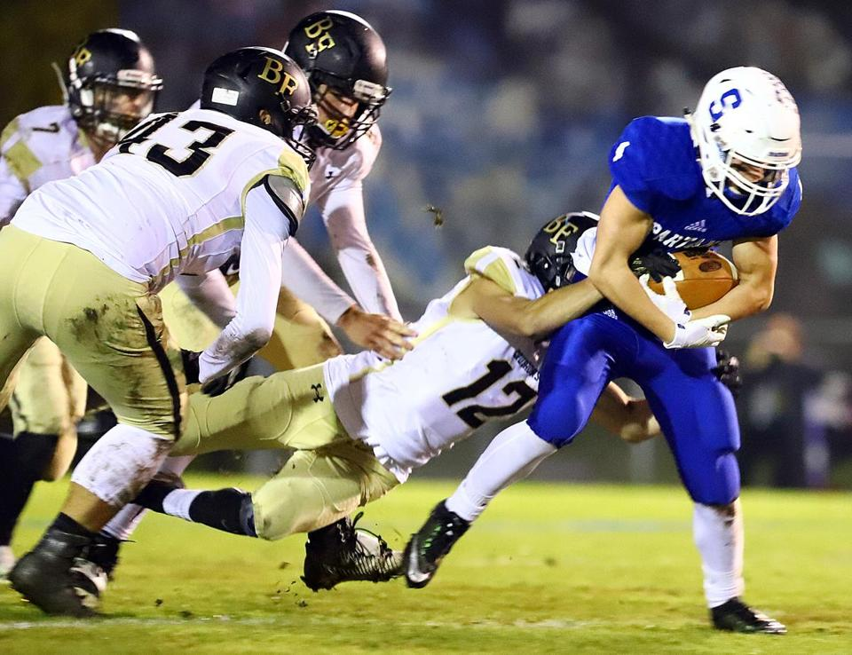 Stoneham's Seth Russell battles for extra yardage against Bishop Fenwick in the Division 6 North football semifinal. Mark Lorenz for the Boston Globe.